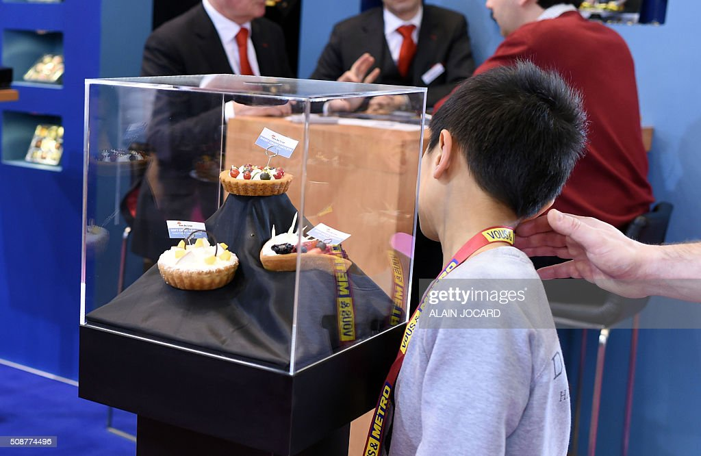 A child looks at pastry on the 'Van Deleur' stand, during the Europain fair, on February 6, 2016, in Villepinte near Paris. / AFP / ALAIN JOCARD