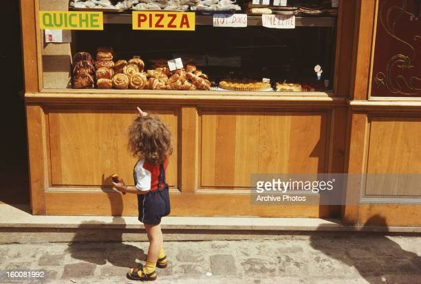 A child looks at the cakes in a patisserie window on the Rue du MontCenis in Paris France July 1975