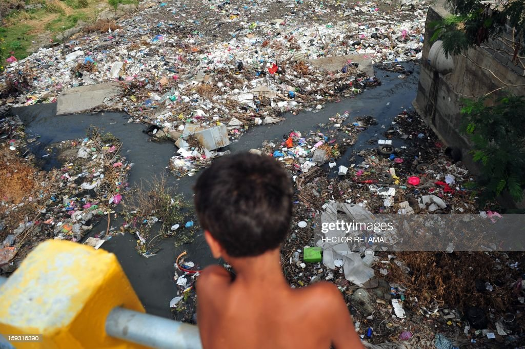 A child looks at the trash that in a small river that flows into Lake Xolotlan, in Managua, on January 11, 2013. AFP PHOTO/Hector RETAMAL