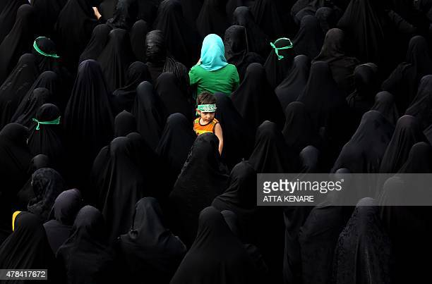 A child looks on as Iranian mourners attend the funeral of Mohammad Hamidi Hasan Ghafari and Ali Amrai all three members of the Islamic Republic's...