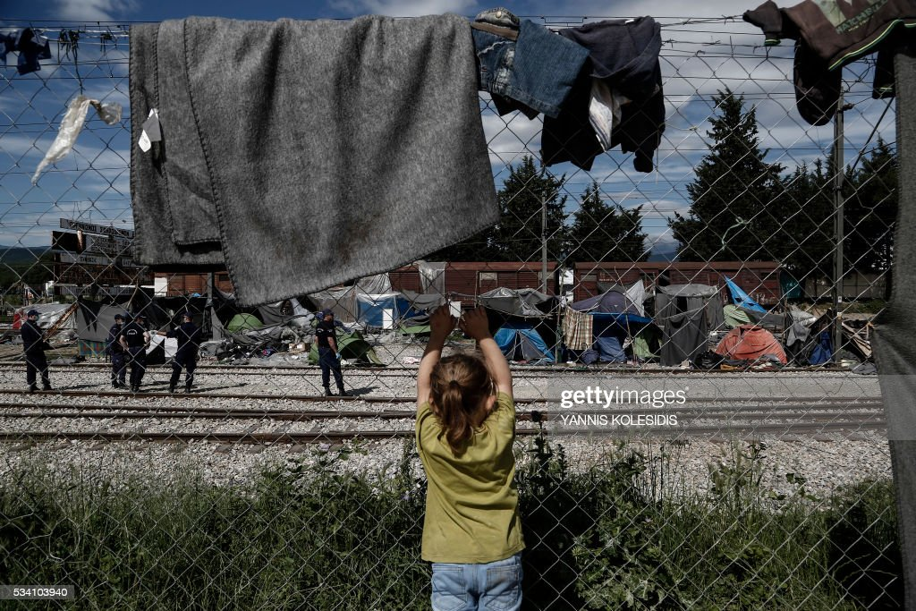 A child looks on as police officers remove tents during a police operation at a refugee camp at the border between Greece and Former Yugoslav Republic of Macedonia (FYROM), near the village of Idomeni, northern Greece on May 25, 2016. Greek police restarted an operation to move migrants out of Idomeni, the squalid tent city where thousands fleeing war and poverty have lived for months. The migrants and refugees were bussed to newly opened camps near Greece's second city Thessaloniki, about 80 kilometres (50 miles) to the south. / AFP / POOL / Yannis KOLESIDIS