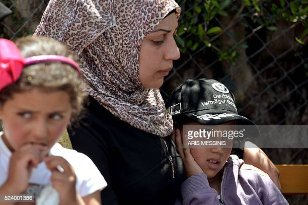 A child looks on as Queen Rania of Jordan speaks to the press during her visit at the refugee site of Kara Tepe in Mytilene on April 25 2016 / AFP /...