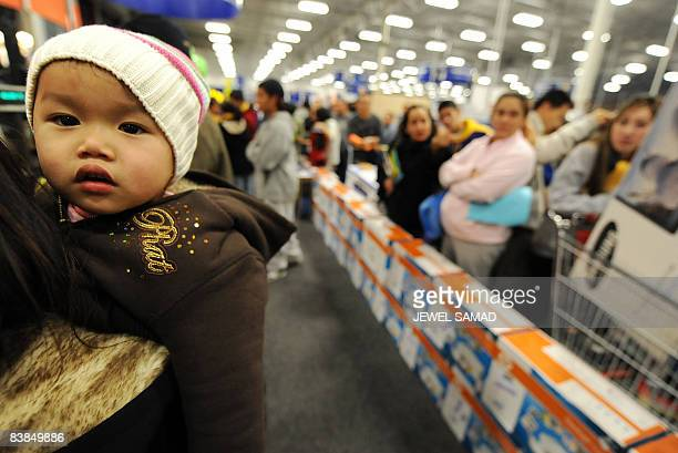 A child looks on as shoppers wait in a queue to pay at a BestBuy store on November 28 2008 in Los Angeles California a day after Thanksgiving...