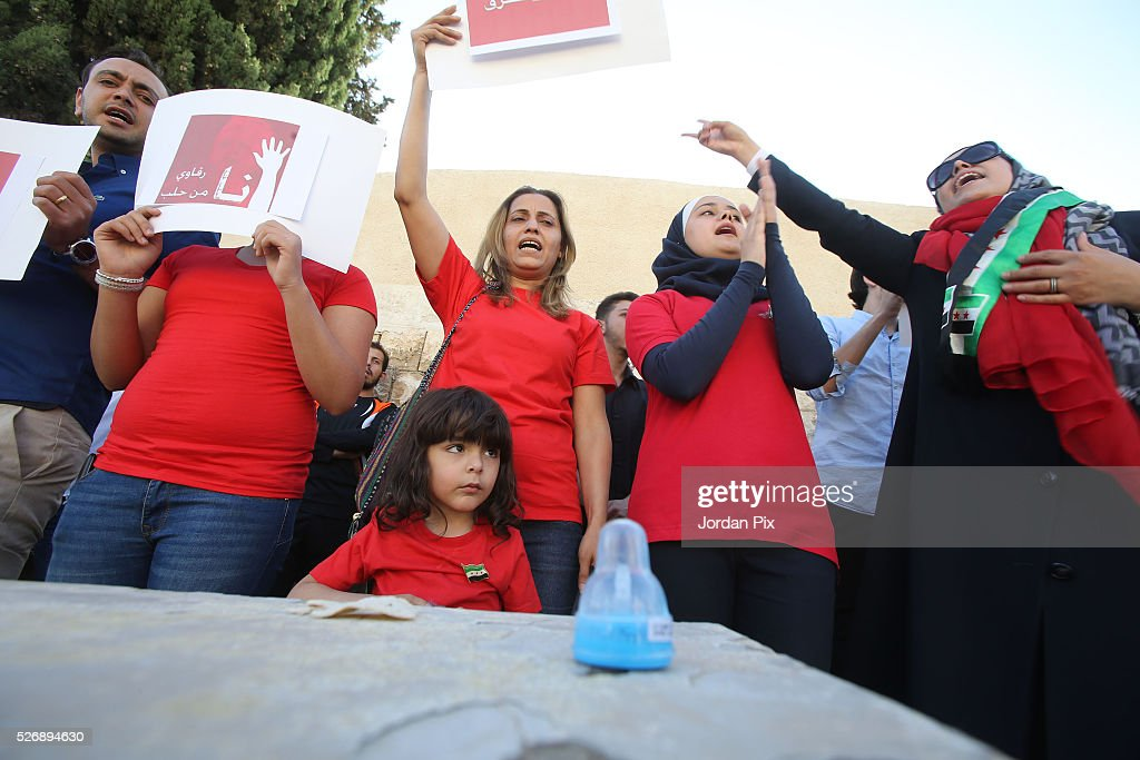 A child looks on as Syrian refugees living in Jordan protest against the world silence towards the air strikes over the northern Syrian city of Aleppo during a sit-in protest in front of the UN Headquarters on May 1, 2016 in Amman, Jordan. According to news reports, many civilians have been killed as a result of airstrikes.