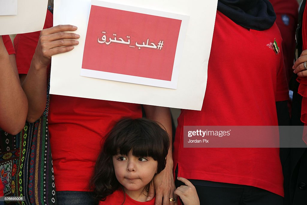 A child looks on as Syrian refugees living in Jordan protest against the world silence towards the air strikes over the northern Syrian city Aleppo during a sit-in protest in front of the UN Headquarters on May 1, 2016 in Amman, Jordan. According to news reports, many civilians have been killed as a result of airstrikes.