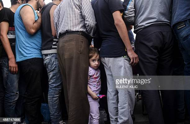 A child looks on as Syrian refugees queue for food as they rest beside the highway on their way to the border between Turkey and Greece in Edirne on...