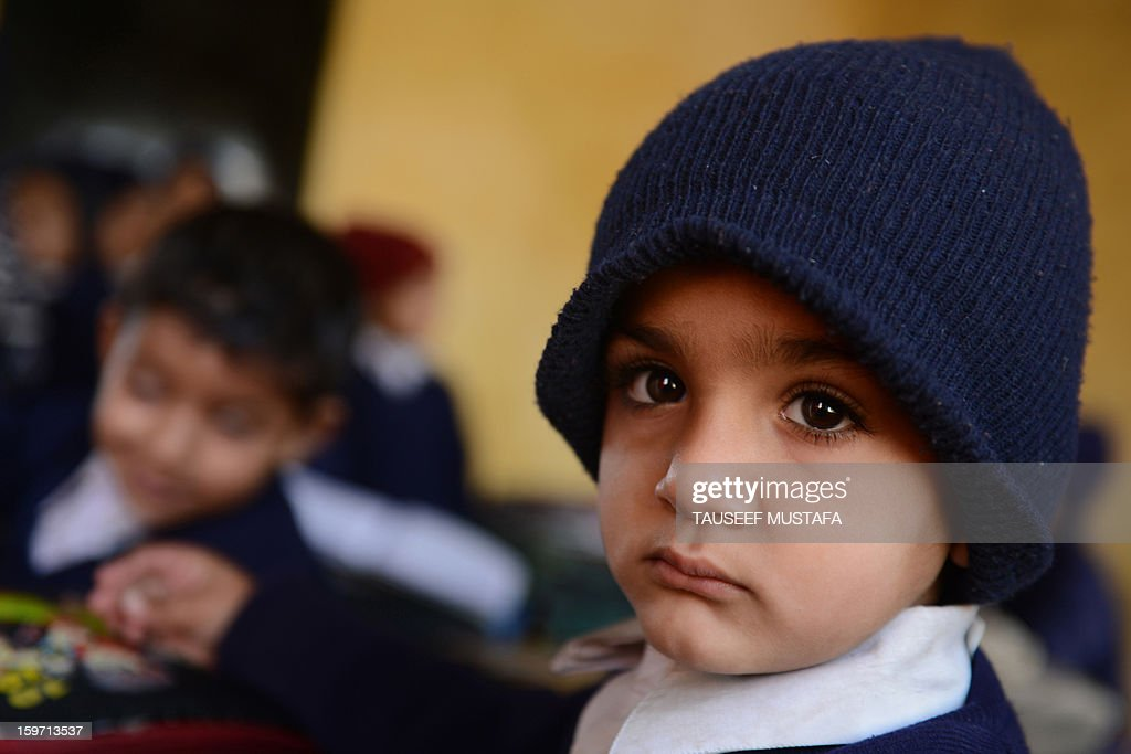 A child looks on at a school near the India-Pakistan border in Gharana, some 35 kms southwest of Jammu, on January 19, 2013. On both sides of the de facto border in Kashmir, villagers living on one of the world's most dangerous flashpoints have special reason to fear the return of tension between India and Pakistan. The spike in cross-border firing in Kashmir -- a region claimed wholly by both India and Pakistan -- has seen five soldiers killed in recent days and threatened to unravel a fragile peace process that had begun to make progress. AFP PHOTO/Tauseef MUSTAFA