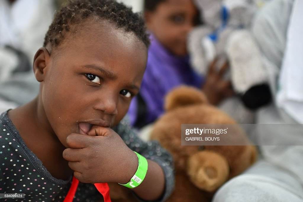 A child looks on during a distribution of meals aboard the rescue ship 'Aquarius', on May 25, 2016 a day after a rescue operation of migrants and refugees off the Libyan coast. The Aquarius is a former North Atlantic fisheries protection ship now used by humanitarians SOS Mediterranee and Medecins Sans Frontieres (Doctors without Borders) which patrols to rescue migrants and refugees trying to reach Europe crossing the Mediterranean sea aboard rubber boats or old fishing boat. / AFP / GABRIEL