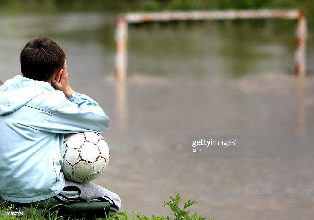 A child looks on June 3, 2010 at his flooded local football field near the eastern Croatian town Slavonski Brod, some 150 kms from the capital Zagreb, after heavy rain caused partial floods in eastern Croatia. AFP PHOTO/CROPIX/Danijel Soldo