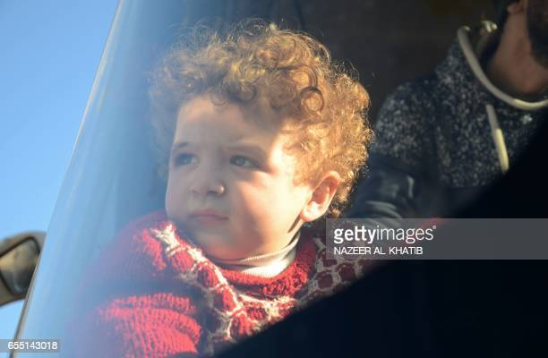 A chils looks our of a bus window as Syrians who were evacuated from Waer the last oppositionheld district of Homs arrive in the northern Syrian town...