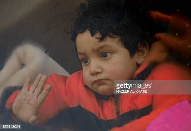 A child looks out of a bus window as Syrians who were evacuated from Waer the last oppositionheld district of Homs arrive in the northern Syrian town...