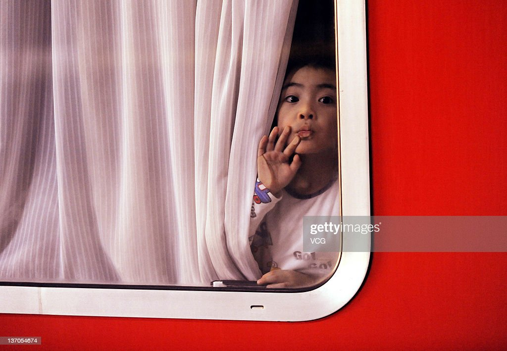 A child looks out of a train window at Shenyang North Railway Station on January 14, 2012 in Shenyang, China. China's annual Spring Festival travel rush began on January 8 as authorities estimate 3.158 billion passenger journeys will be made for the Chinese lunar new year during the 40-day travel period.