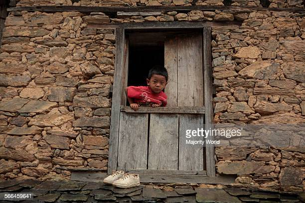 A child looks out of the window of his home in Bandipur Nepal June 26 2010 Bandipur is a hilltop settlement in Tanahu District at an elevation of...