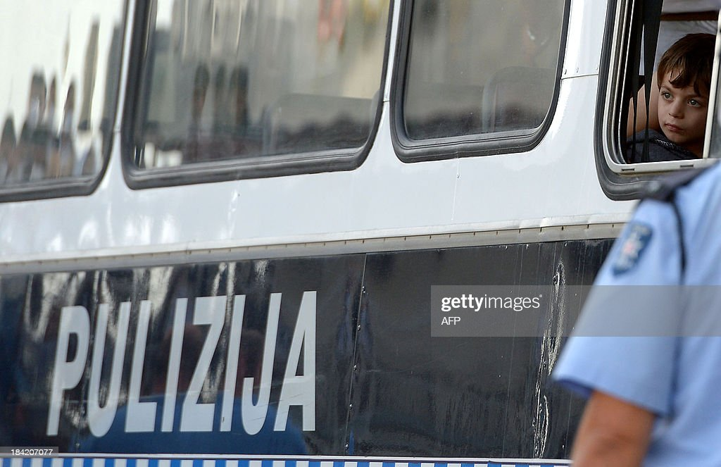 A child looks out the window of a police bus carrying migrants who were rescued by the Armed forces of Malta at Hay Wharf in Valletta on October 12, 2013. More than 140 survivors, plucked from the sea after their overloaded boat sank in the latest deadly migrant tragedy to hit the Mediterranean, arrived in Malta. The sinking killed more than 30, most of them women and children, when the boat packed with people desperate to reach European shores went down off Malta near the Italian island of Lampedusa, according to officials.