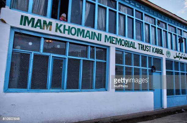 Child looks out the window of the Imam Khomeini Memorial Trust building in the town of Kargil Ladakh Jammu and Kashmir India