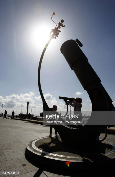A child looks through a Telescope at The Albert Dock Liverpool as the sunny weather continues across the UK
