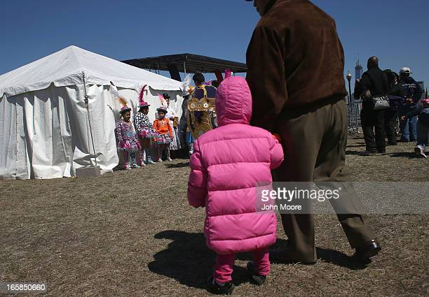 A child looks towards a group of Bolivian dancers in a 'Time is Now' rally for national immigration reform on April 6 2013 in Jersey City New Jersey...