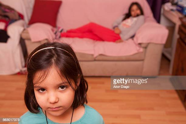 Child looks worried. Sister lying on the sofa