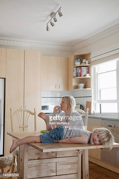 child lying on kitchen table, mum in background