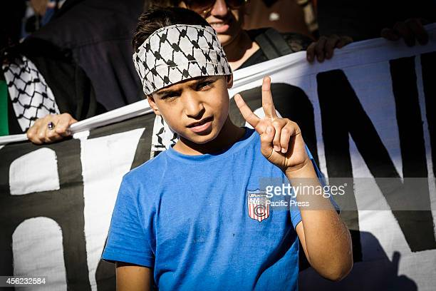 A child makes a 'Peace' sign during a demonstration in Rome to denounce Israel's military campaign in Gaza and to show support to the Palestinian...