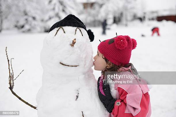 Child makes a snowman in winter