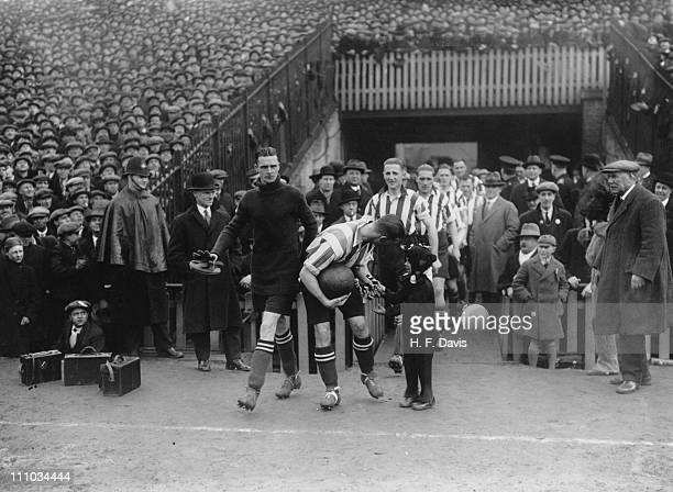 A child mascot dressed as a cat hands a lucky horseshoe to Southampton captain Michael Keeping before an FA Cup Sixth Round tie against Millwall at...
