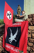 A child member of South African selfstyled racist white supremacist Afrikaner Weerstandsbeweging AWB holds AWB flag as his hooded comrade stands...