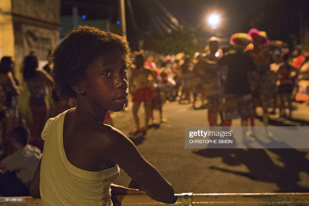 A child member of the local 'Indio' carnival group of the Guadalupe neighborhood in northern Rio de Janeiro, Brazil, awaits to take part in their 'Bate Bola' traditional parade on February 10, 2013. AFP PHOTO/Christophe Simon