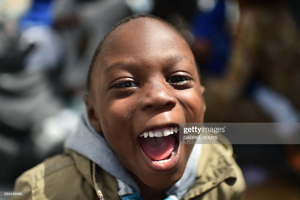 A child migrant laughs prior to leave rescue ship 'Aquarius' as more than 380 migrants arrive in the port of Cagliari, Sardinia, on May 26, 2016, two days after being rescued near the Libyan coasts. The Aquarius is a former North Atlantic fisheries protection ship now used by humanitarians SOS Mediterranee and Medecins Sans Frontieres (Doctors without Borders) which patrols to rescue migrants and refugees trying to reach Europe crossing the Mediterranean sea aboard rubber boats or old fishing boat. / AFP / GABRIEL