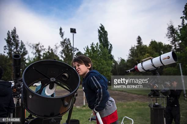 A child observes the sky through a telescope during a tour at the Astronomic Center 'Cielos Chilenos ' in Colina some 20 kilometres North of Santiago...