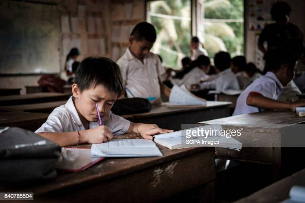 A child of Chinese ethnicity studies in a mixed classroom composed of two year groups There are sixteen ethnic groups in Cambodia's Ratanakiri and...