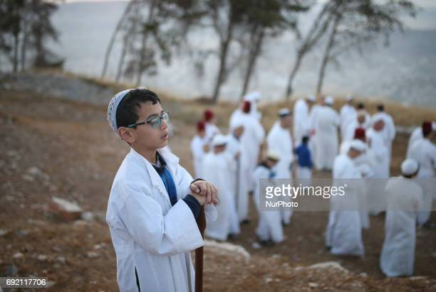 A child of the Samaritan community prays as he prepares to take part in the traditional pilgrimage marking the holiday of Shavuot atop Mount Gerizim...