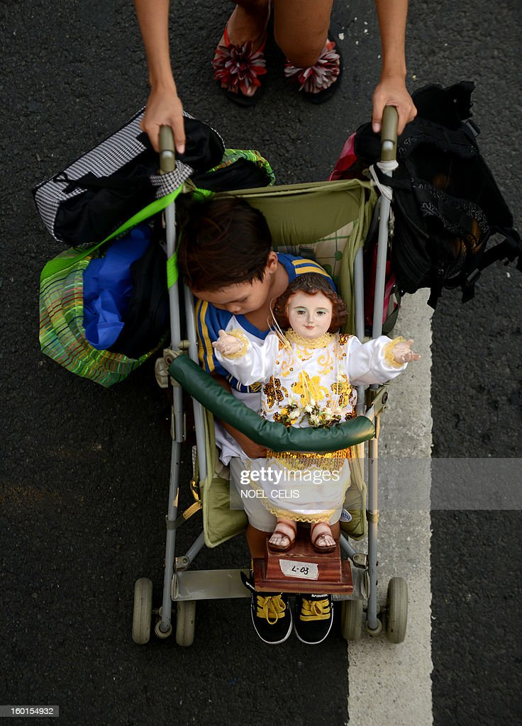 A child on a stroller sleeps beside a religious icon of the baby Jesus Christ during the annual Grand Santo Nino Procession in Manila on January 27, 2013. The annual Grand Santo Nino Procession features almost 300 floats with different images of the child Jesus Christ flown in from various parts of the country. The Philippines is Asia's bastion of Catholicism and the Sto Nino feast is one among dozens of religious festivals honouring various saints and religious icons, a legacy of three centuries of Spanish rule across the archipelago.
