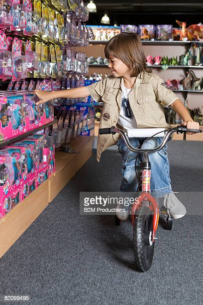 Child (4-5 years ) on bicycle in toy store