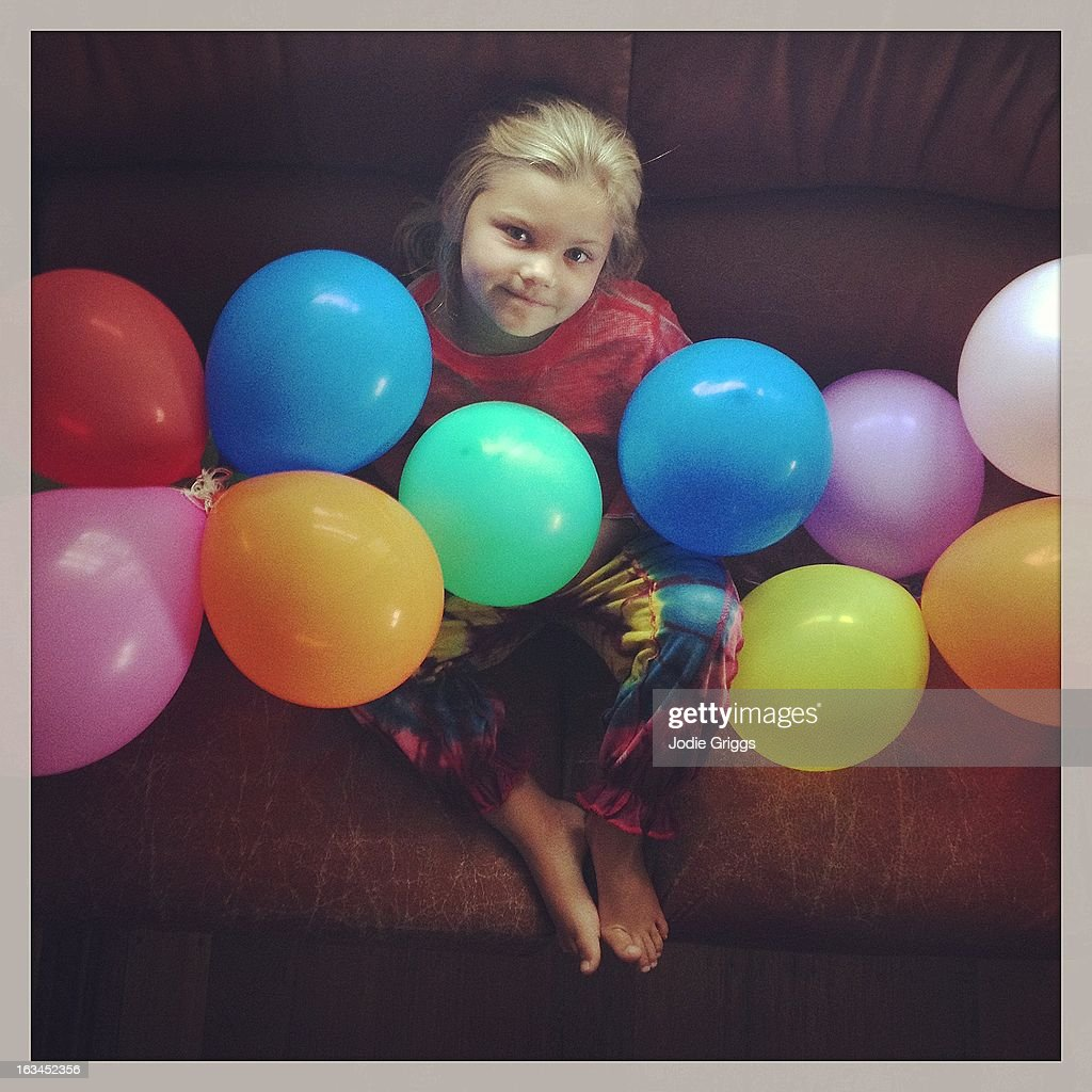 Child on couch surrounded by colourful balloons : Stock Photo