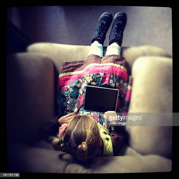 Child on couch with digital tablet