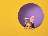Cute little child wearing bunny ears on Easter day. Girl on yellow and violet background.