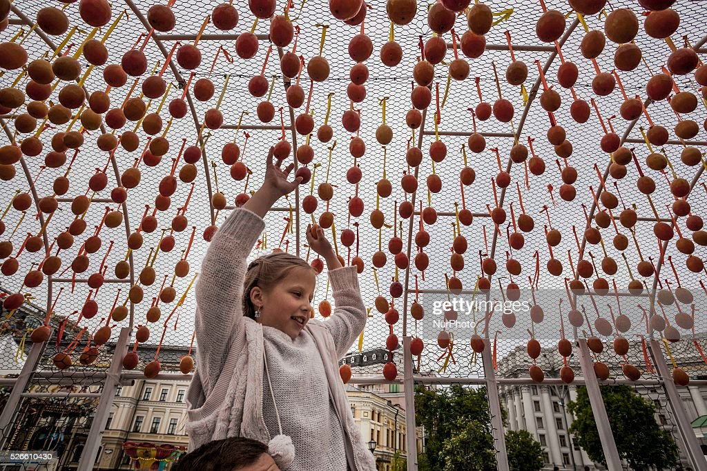 Child on father shoulder touches Easter eggs hanged in a passage in Kiev, Ukraine, to get luck. on 30 April 2016.