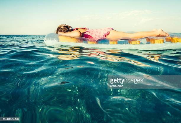 Bambino sul materasso gonfiabile in mare blu galleggiante