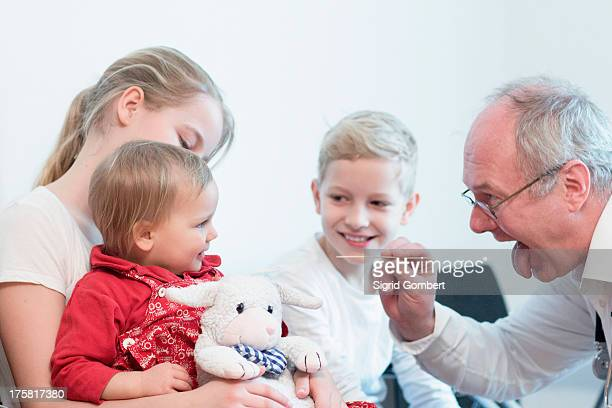 Child on sister's lap being examined by doctor