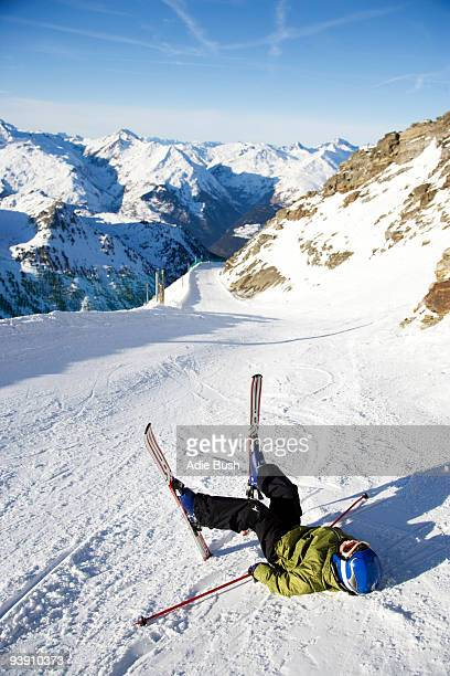 Child on skis lying in the snow.