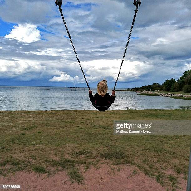 Child On Swing Against River And Cloudy Sky