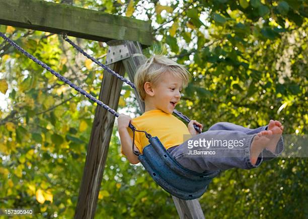 Child on swing in midst of trees on sunny day