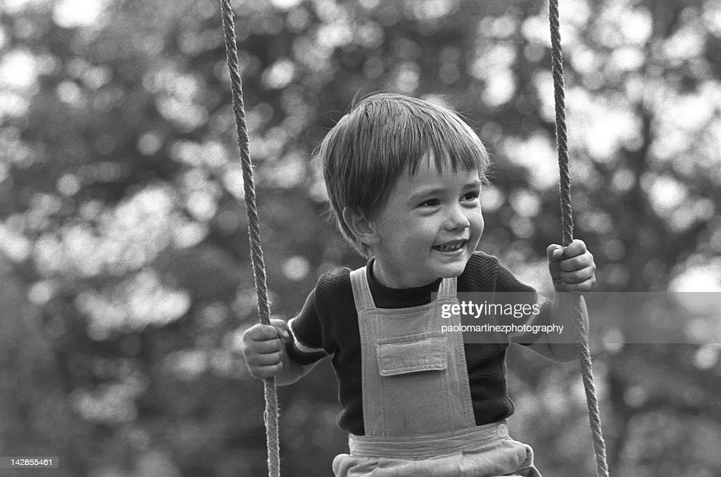 Child on swing in summer : Stock Photo