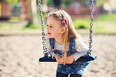 Children playground. Cute little girl having fun with a swing in the park