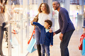 Child On Trip To Shopping Mall With Parents Pointing And Smiling To Shop Window