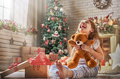 Happy holidays! Cute little child opening present near Christmas tree. The girl laughing and enjoying the gift.