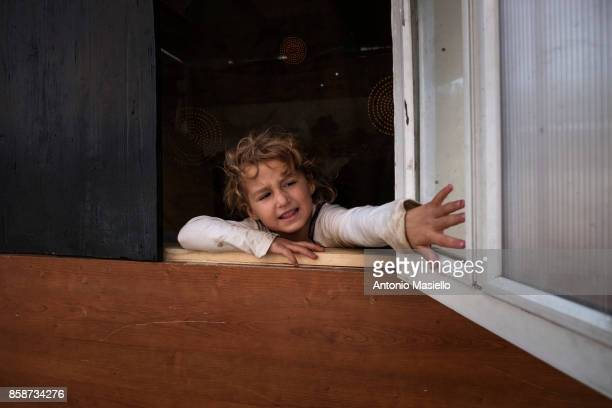 A child opens the window of their room in an occupied building on October 4 2017 in Rome Italy For the last 5 years hundreds of people including...
