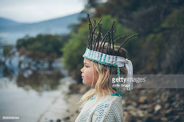 Child outside wearing crown made from sticks