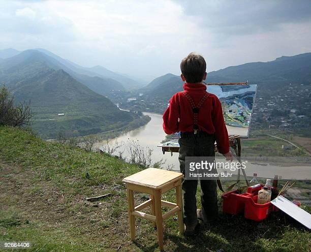 Child painting a Caucasus landscape